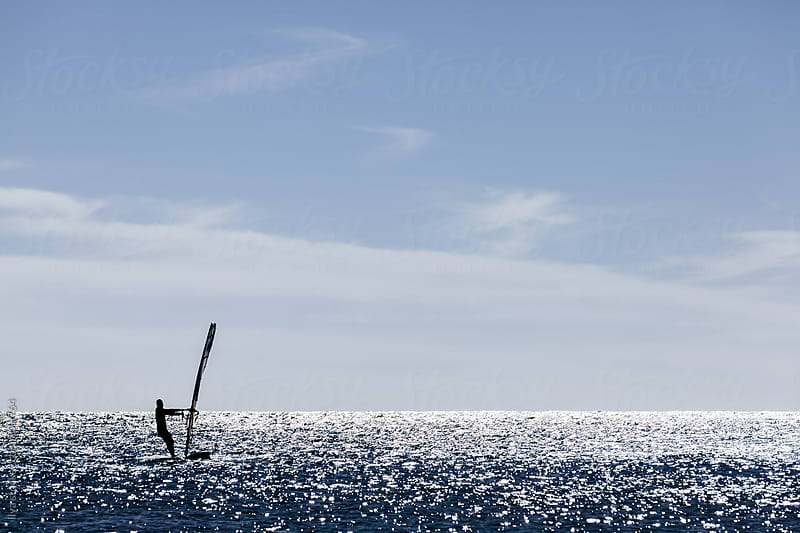 Unrecognizable man wind surfing in red sea by Ilya for Stocksy United