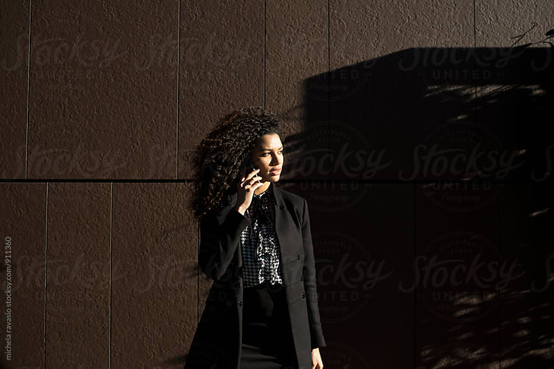 Portrait of young business woman on the cell phone outdoors by michela ravasio for Stocksy United