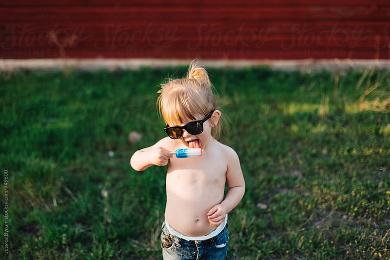 Toddler girl eating popsicle with sunglasses on by Jessica Byrum for Stocksy United