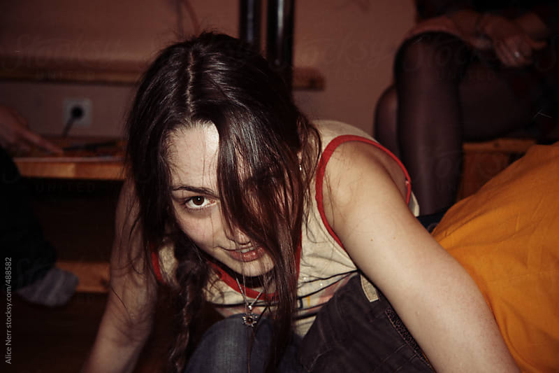 Young lady smiles while finding herself in a twisted position playing games with friends by Alice Nerr for Stocksy United