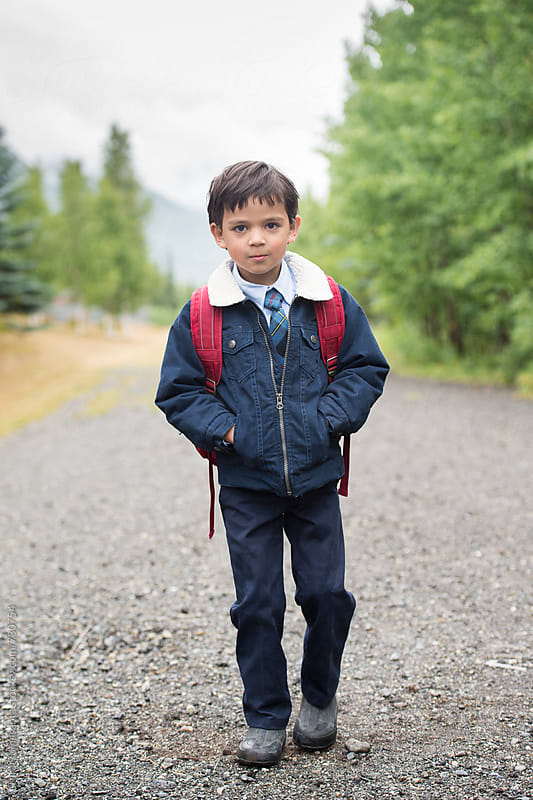 young boy walks to school on a stone path by Tara Romasanta for Stocksy United