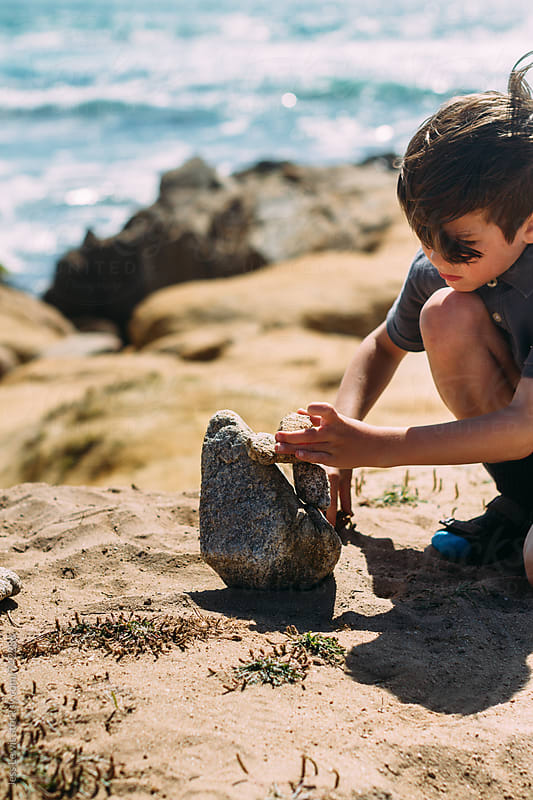 boy building a cairn on the coast by Jess Lewis for Stocksy United