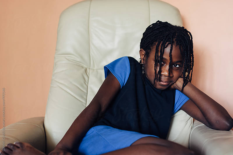 Smiling black girl sitting in a chair by Gabriel (Gabi) Bucataru for Stocksy United