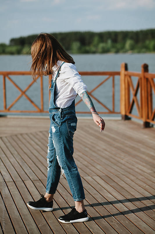 Beautiful brunette woman walking in pier  by Sergey Filimonov for Stocksy United