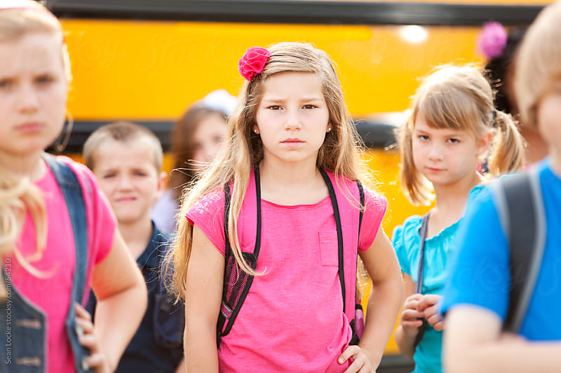 School Bus: Focus on Girl with Serious Look by Sean Locke for Stocksy United