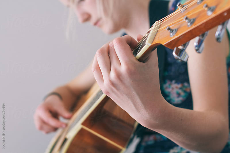 Girl Playing a Guitar by Jacqui Miller for Stocksy United