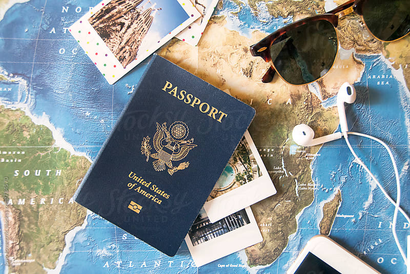 Passport, sunglasses and Polaroid pictures on a world map by Jovo Jovanovic for Stocksy United