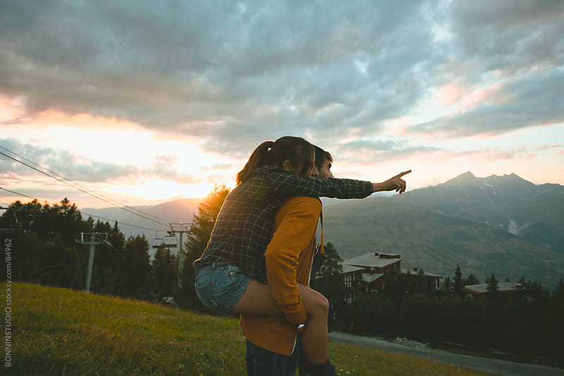 Young Man Piggybacking His Girlfriend On beautiful sunset landscape. by BONNINSTUDIO for Stocksy United