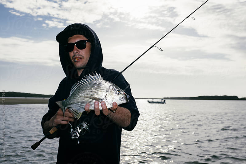Angler with a Smoke hanging from his Mouth with a Bream by Gary Radler Photography for Stocksy United