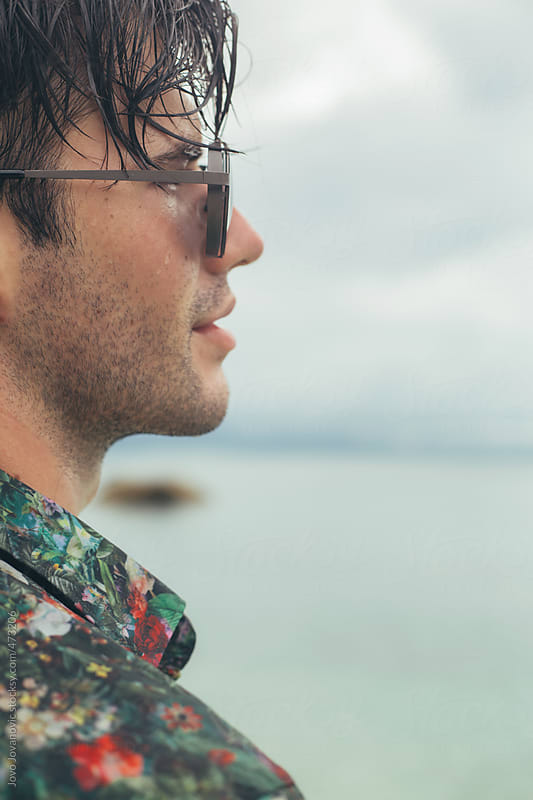Close up of serious young man with sunglasses on with the ocean in the background by Jovo Jovanovic for Stocksy United