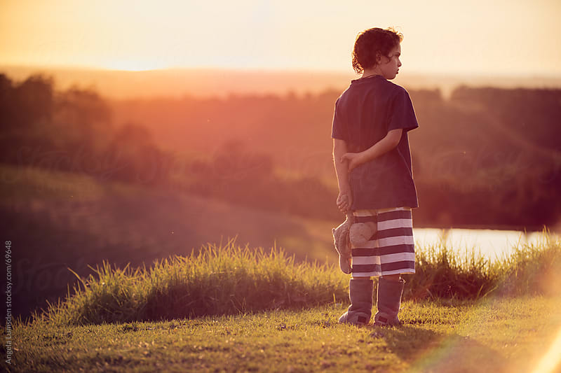 Young boy standing with his teddy bear in the country at sunset by Angela Lumsden for Stocksy United