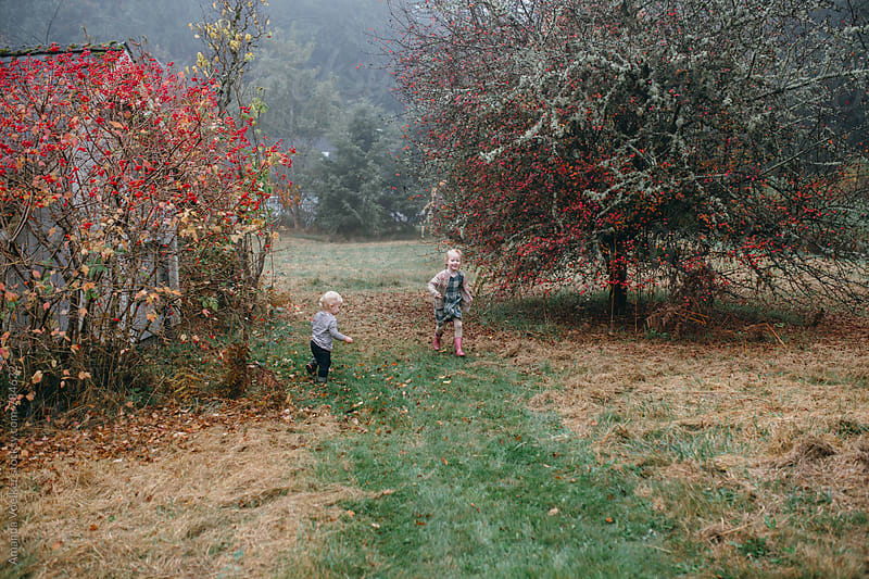 A little brother and sister run through a farm path in fall by Amanda Voelker for Stocksy United
