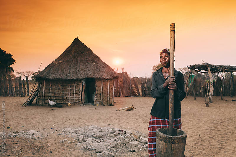 African Hambukushu woman pounding corn by Micky Wiswedel for Stocksy United