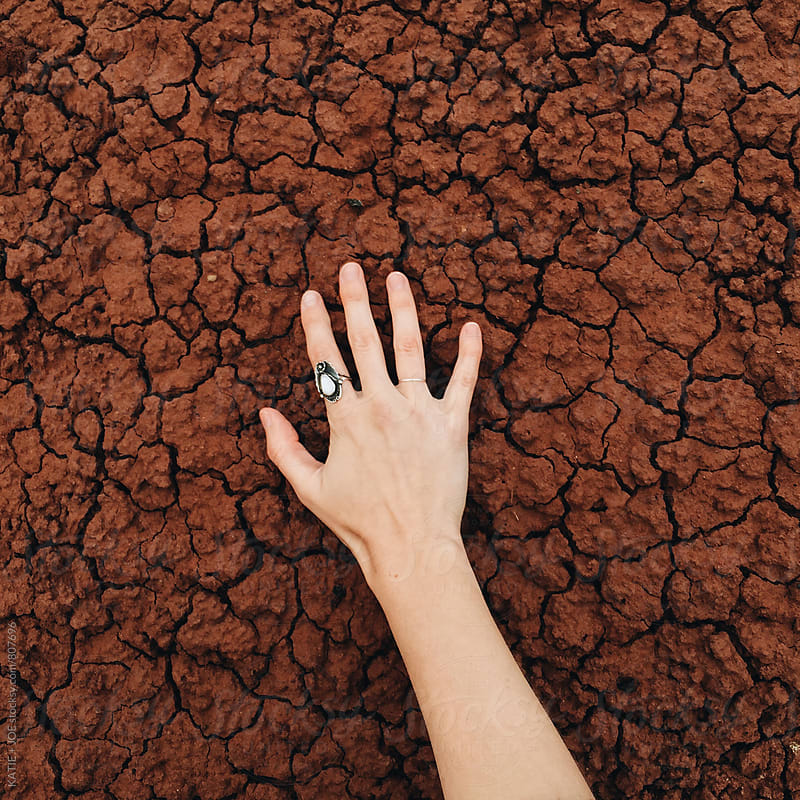 Hand on a cracked, clay surface by KATIE + JOE for Stocksy United