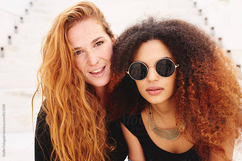 Redhed freckled woman with her afro friend by Guille Faingold for Stocksy United