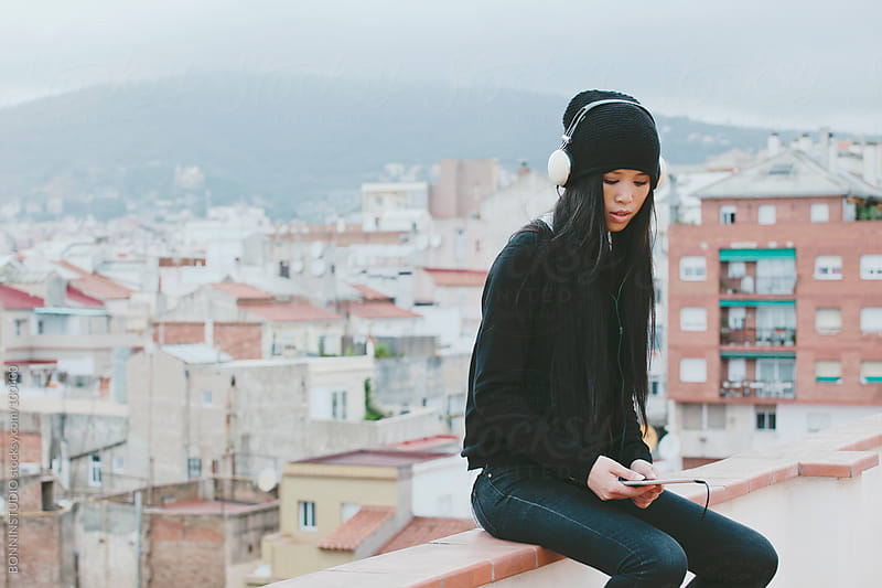 Young chinese woman listening music on tablet sitting on rooftop. Winter scene. by BONNINSTUDIO for Stocksy United