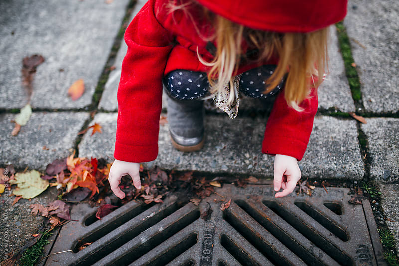 A Little Girl Crouches By the Sewer And Drops in Stones by Amanda Voelker for Stocksy United