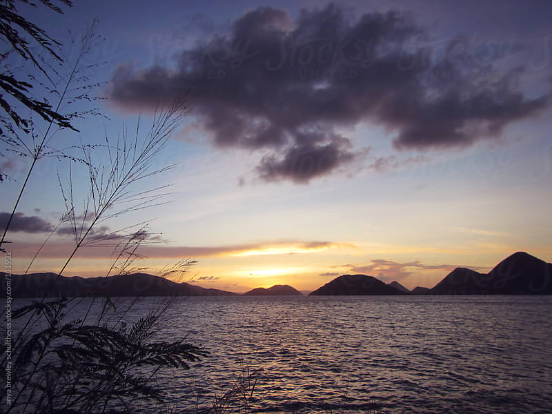 Sunset on the sea with islands in the background by anya brewley schultheiss for Stocksy United