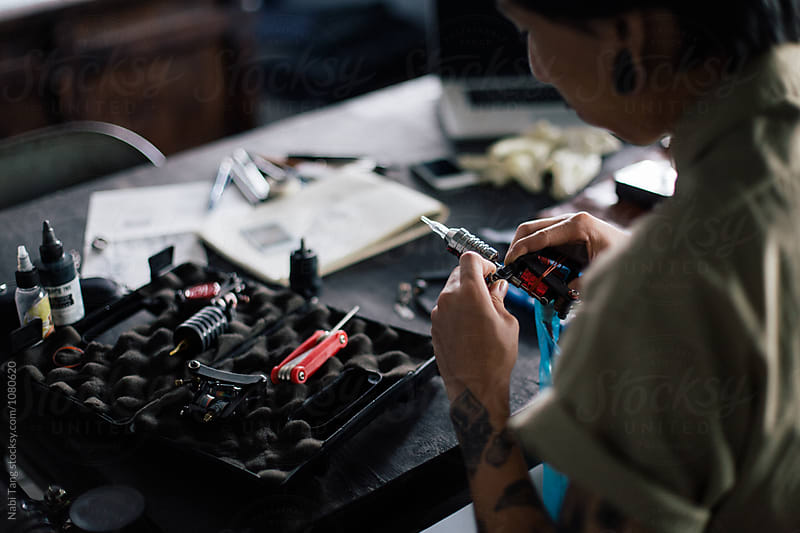 Tattoo artist in working in the studio by Nabi Tang for Stocksy United