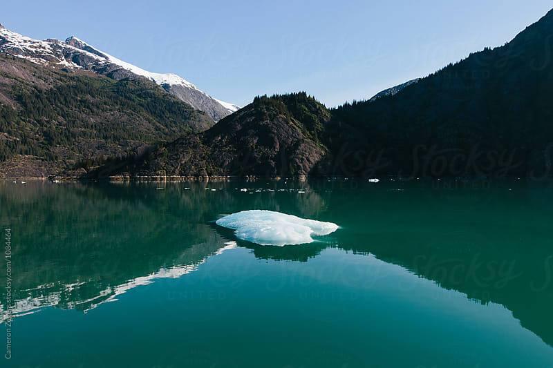 iceberg floating in calm water by Cameron Zegers for Stocksy United