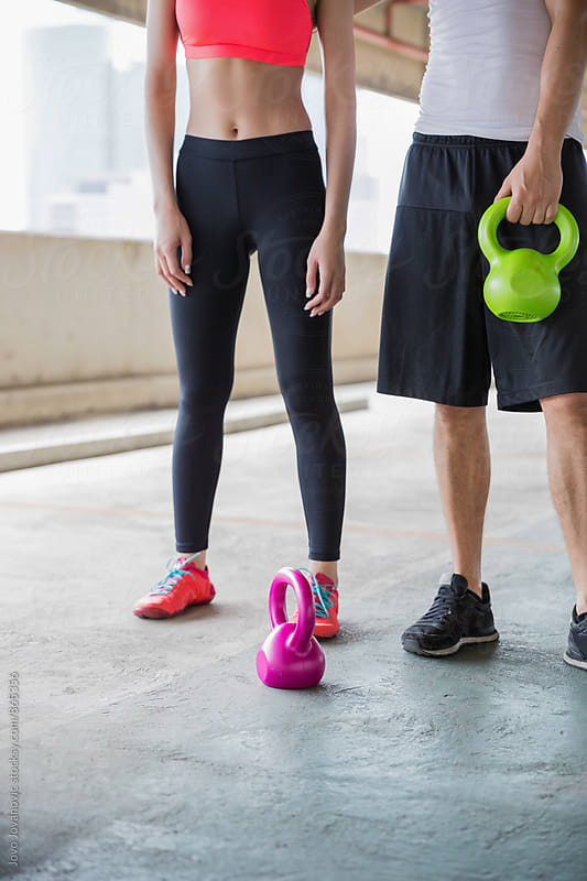 Closeup of two young people working out with kettlebells  by Jovo Jovanovic for Stocksy United