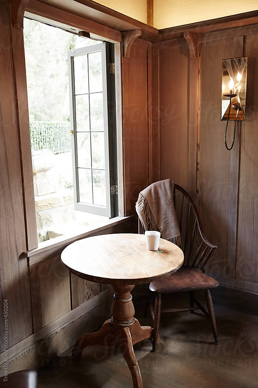 Table and chair with tea in cozy wood room near window  by Trinette Reed for Stocksy United