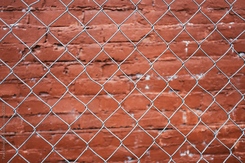 Chain-link fence in front of painted brick wall by Paul Edmondson for Stocksy United