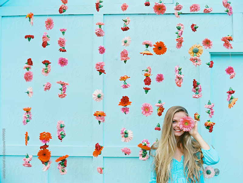 blonde girl in front of pink floral wall with flower over eye by wendy laurel for Stocksy United