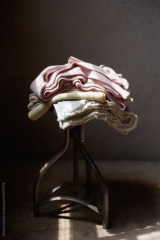 Stack of home fabrics on a stool by Miquel Llonch for Stocksy United