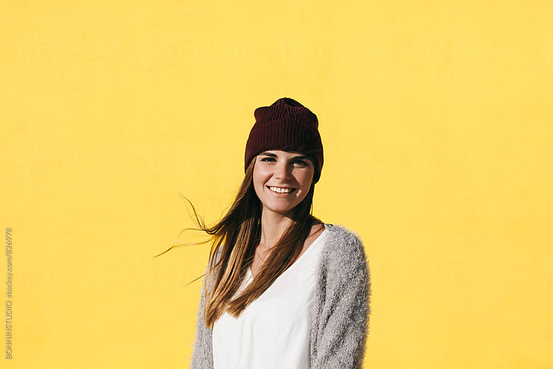 Portrait of a smiling caucasian woman standing in front of a yellow wall. by BONNINSTUDIO for Stocksy United