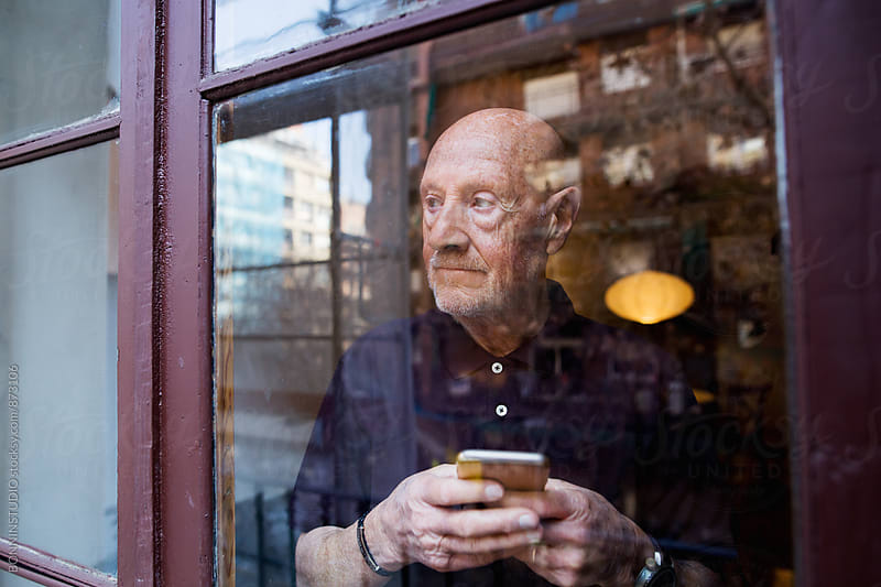 Elderly man holding a phone looking through the window. by BONNINSTUDIO for Stocksy United