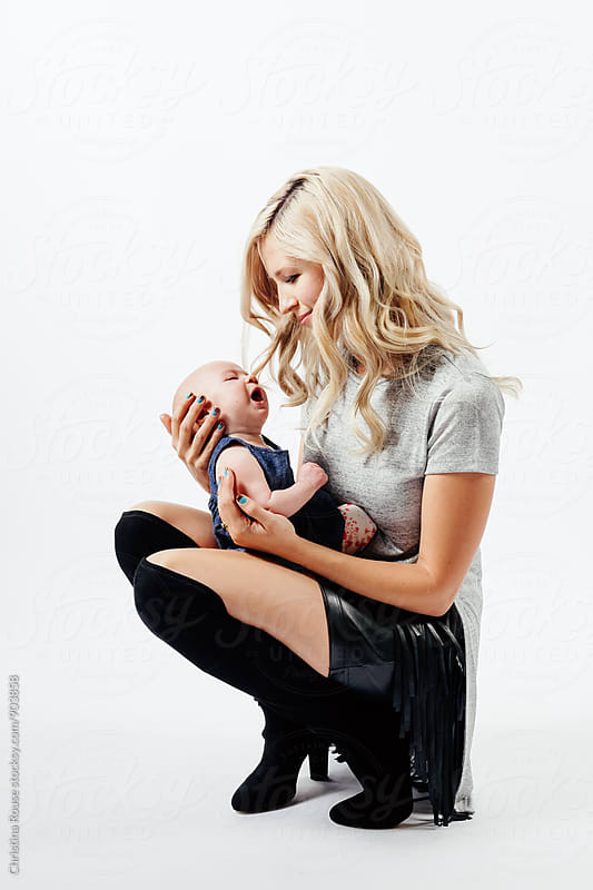 Mom cradles baby on her lap by Christina Rouse for Stocksy United