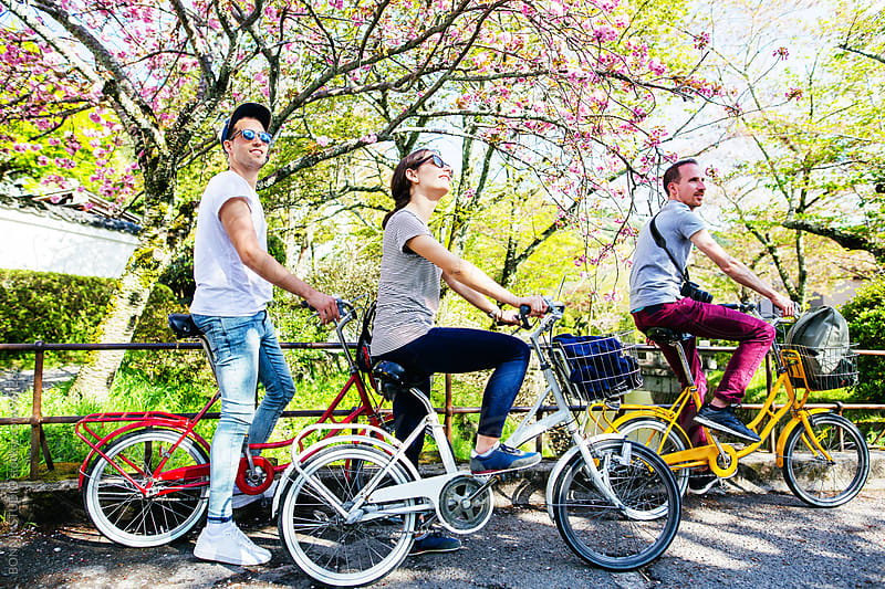 Side view of tourist friends on bicycle in spring. by BONNINSTUDIO for Stocksy United