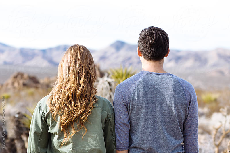 Couple facing away from the camera in desert by Melanie Riccardi for Stocksy United