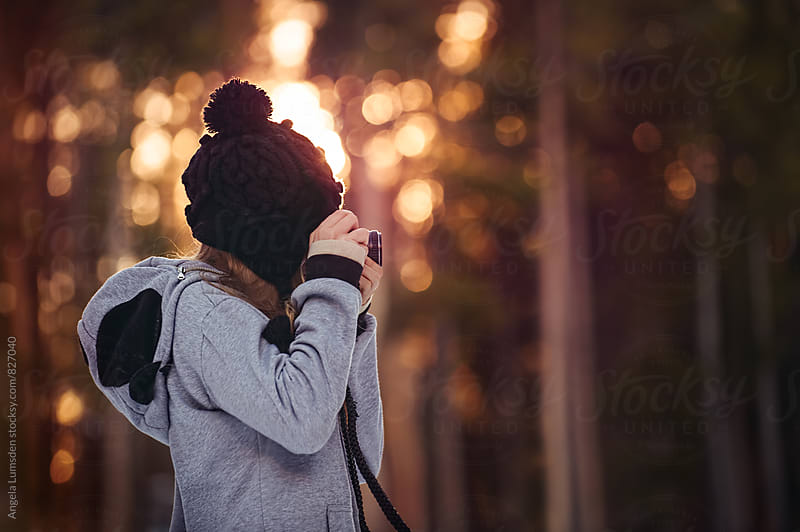 Teenage girl with a black beanie taking a photo in sunset light in winter by Angela Lumsden for Stocksy United