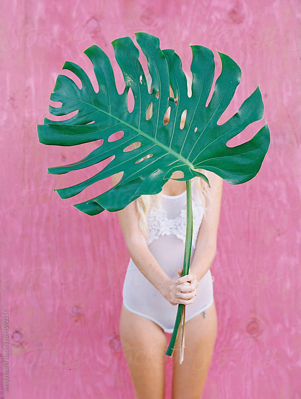 girl in white holding palm leaf in front of her against pink wall by wendy laurel for Stocksy United