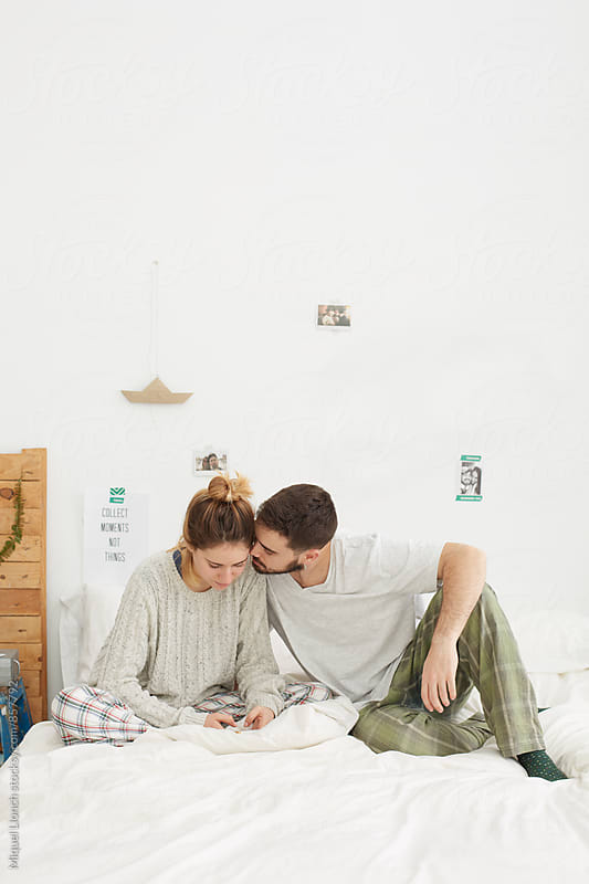 Young couple in her bedroom browsing with the phone by Miquel Llonch for Stocksy United