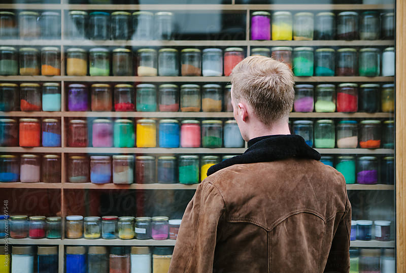Blonde man next to a shop window filled with artists powder paints of many colours. by kkgas for Stocksy United