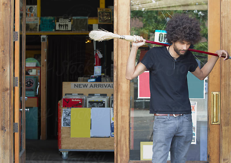 Young man with broom at record shop by Andersen Ross Photography for Stocksy United