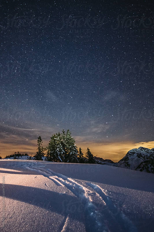 traces in snowcovered landscape under starry night by Leander Nardin for Stocksy United