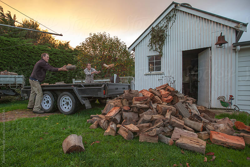 Twin Woodcutters delivering wood by Rowena Naylor for Stocksy United