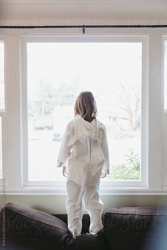 Girl in unicorn costume staring out the window by Rob and Julia Campbell for Stocksy United