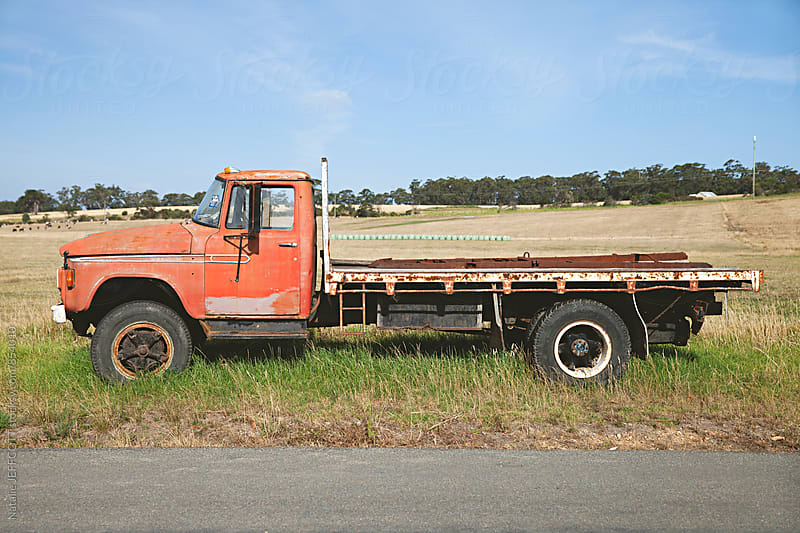Old pick up / flat tray truck on the side of a country road in Australia by Natalie JEFFCOTT for Stocksy United