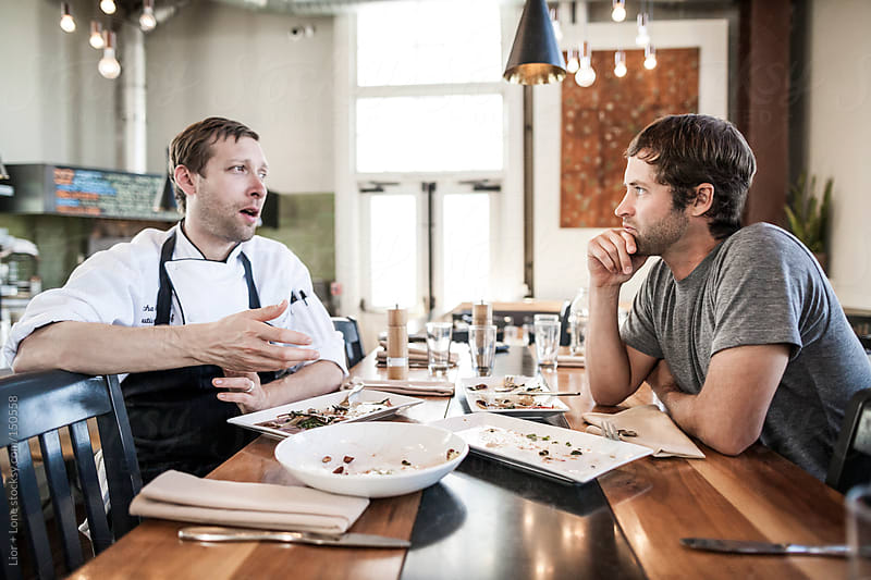 Chef and shift manager conversing after a meal by Lior + Lone for Stocksy United