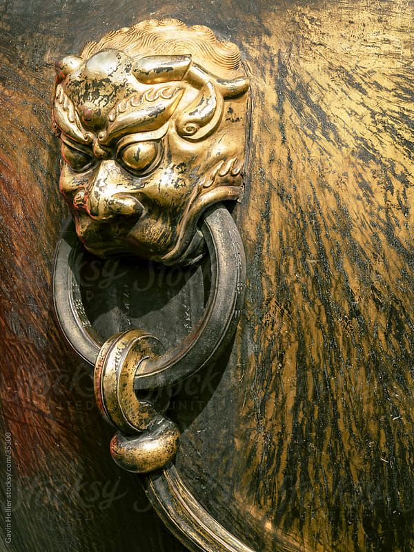 China, Beijing, The Forbidden City, Gugong or Imperial Palace, Brass decorations in the shape of a lion's head knocker or handle by Gavin Hellier for Stocksy United