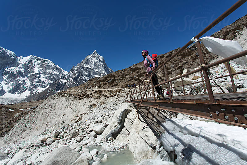 Female trekker standing on steel hanging bridge. by Dejan Ristovski for Stocksy United