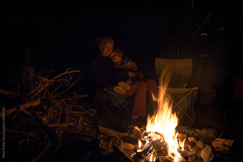 Toddler sleeping on mothe by campfire by Mick Follari for Stocksy United