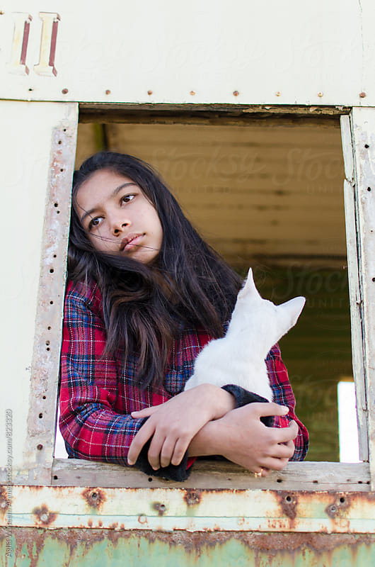 A girl child sitting besides a train window holding her white kitten ! by Agha Waseem Ahmed for Stocksy United