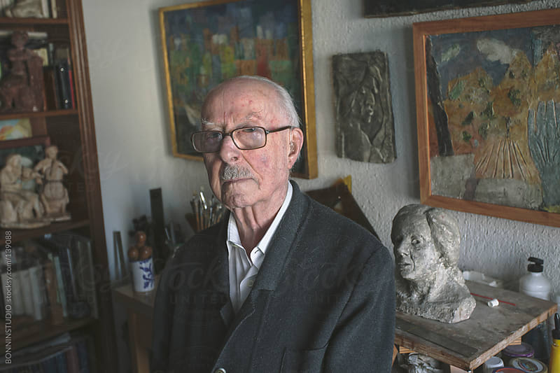 Portrait of old man standing on his studio of painting and sculpture. by BONNINSTUDIO for Stocksy United