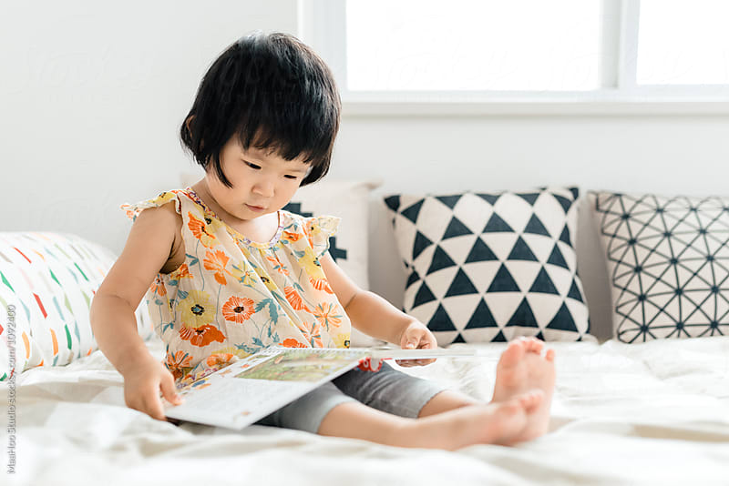 Cute toddler girl reading book on bed by Maa Hoo for Stocksy United